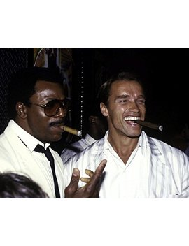 "Globe Photos Art Prints Arnold Schwarzenegger And Carl Weathers Smoking Cigars   14"" X 11"" Pop Culture Art Photographic Full Bleed Print   Premium Paper   80's Retro by Globe Photos Art Prints"